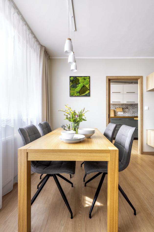 Dřevěný jídelní stůl umístěný v obýváku vyřešil problém s nedostatkem místa v kuchyni
