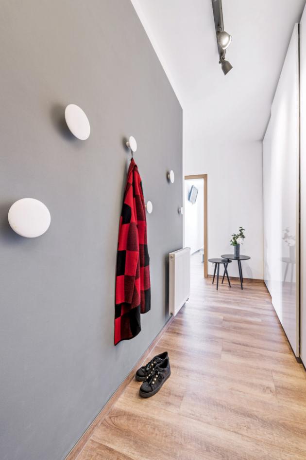 PŘEDSÍŇ Většinu úložného prostoru řeší vysoká vestavěná skříň vyrobená na zakázku. Vtipným prvkem jsou bílé kulaté věšáčky na protější stěně, které si nechala Aneta také vyrobit