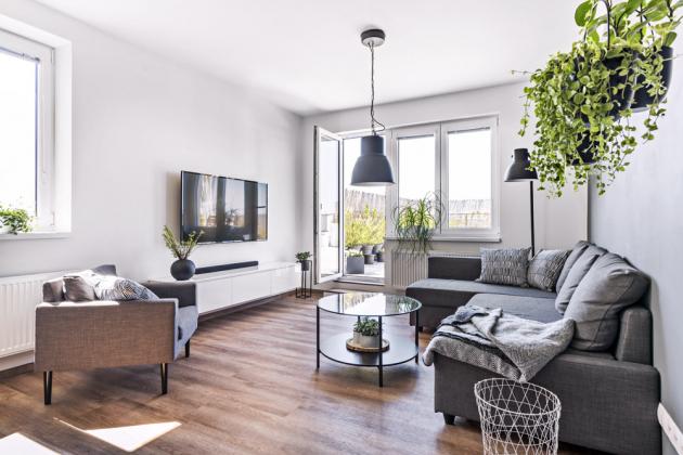OBÝVACÍ ČÁST Převažující bílou barvu doplňují šedé a antracitové odstíny. Rozkládací sedačka, konferenční stolek a osvětlení jsou z IKEA