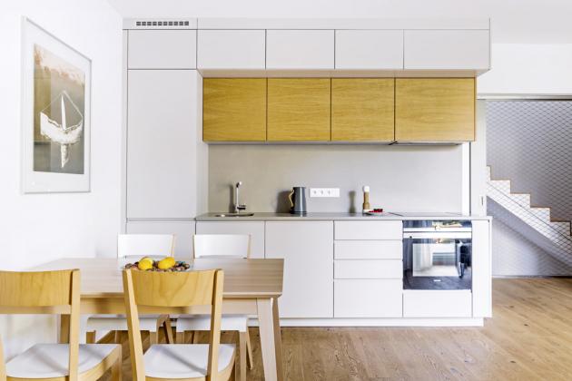 U sestavy výrobce JN Interiér je bíle lakovaný povrch nábytku kombinovaný se světlou dubovou dýhou, stejná barevná kombinace s převahou dřevěných ploch je použita i u jídelní sestavy, www.jninterier.cz