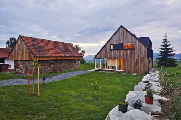 Dřevostavba je umístěna v lokalitě, kde není o tradiční venkovská stavení nouze. Tuto skutečnost bylo nutné respektovat