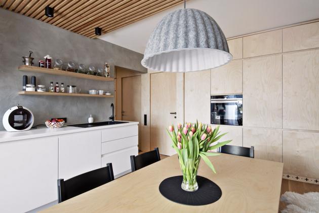 Zpestřujícím prvkem je i betonová stěrka použitá na zdi za kuchyní, přecházející až do obytné části