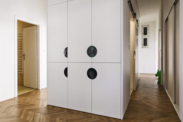 Uprostřed dispozice bytu se za posuvnými dveřmi nachází vyzděný modul s bílou koupelnou