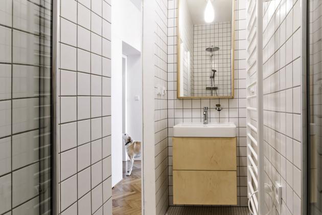 Bíle obložená koupelna nabízí sprchový kout a umyvadlo se skříňkou. Ve žluté koupelně je vana a toaleta s umývátkem