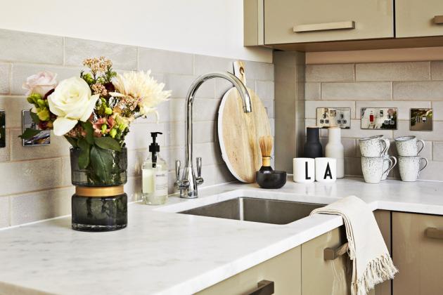 Decentní ženský styl drží i velmi jednoduchá menší kuchyň s dvířky v barvě cappuccina a bílou mramorovou deskou.