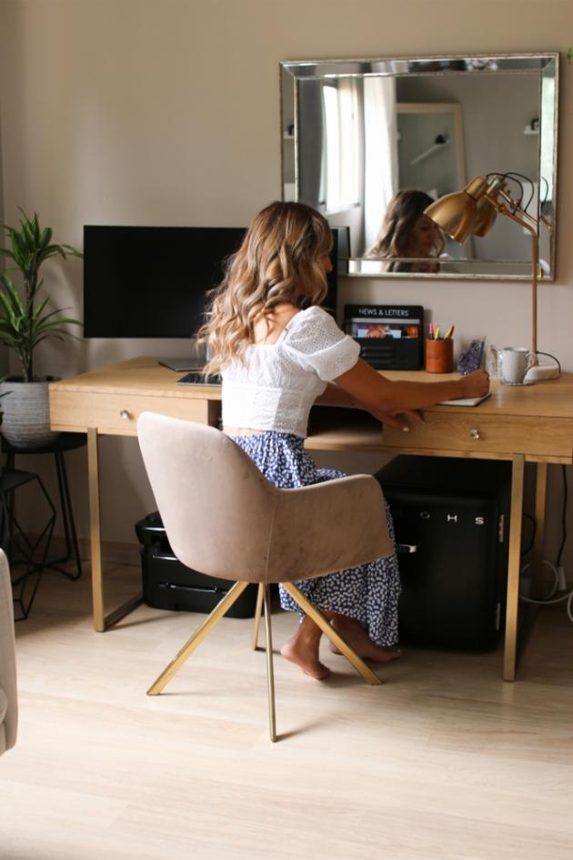 Minimalistický dřevěný stůl, na kterém jsou jen samé potřebné věci: velká obrazovka, zlatá lampa a organizér na psací potřeby. Zlato je originálním prvkem na nohách stolu a na židli.