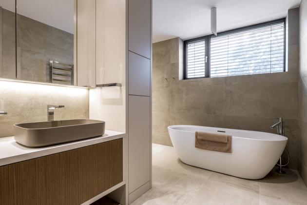 Větší změnu oproti původnímu návrhu jsem udělal také u manželské ložnice, ke které jsme s týmem přidružili velkorysou koupelnu se solitérně koncipovaným sprchovým koutem a vanou.