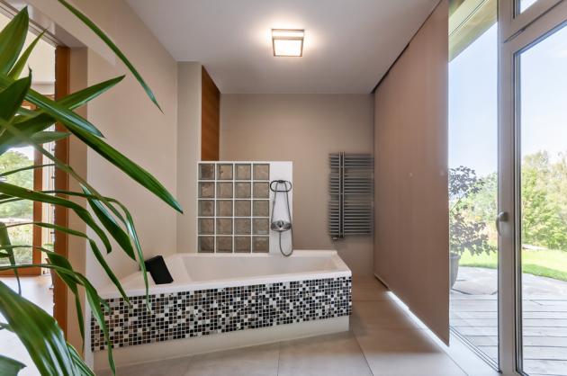 Z obývacího pokoje se vchází do ložnice majitelů, na kterou navazuje koupelna se sprchovým koutem i vanou, sauna a technická místnost. I z koupelny se dá projít rovnou na západní terasu a do zahrady.
