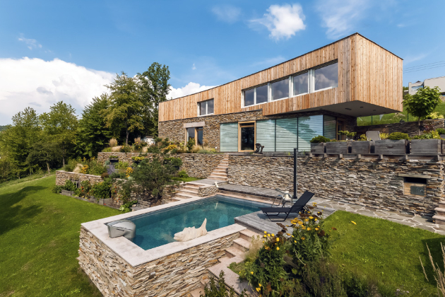 Monumentálně vyhlížející dům je funkční stavbou, která z velké části využívá přírodní materiály, jako je kámen a modřínové dřevo.